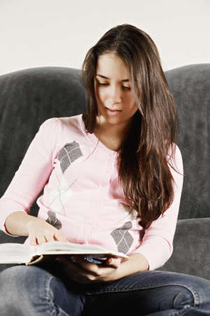 cosiness: Young brunette caucasian woman in pink jersey and blue jeans reading book while sitting on sofa