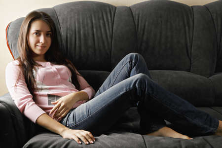 cosiness: Young serene caucasian brunette woman in pink sweater and blue jeans on sofa