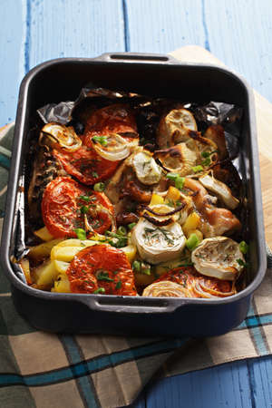 oven tray: Oven tray with baked chicken with vegetables over wooden tabletop Stock Photo