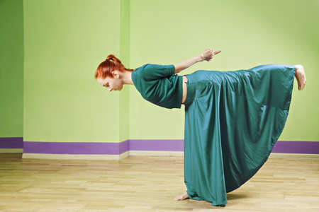 Caucasian redhead dancer in green dress forming staight line while standingf on one leg Stock Photo