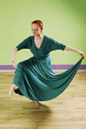 pleasant emotions: Caucasian redhead woman dancing in a green room