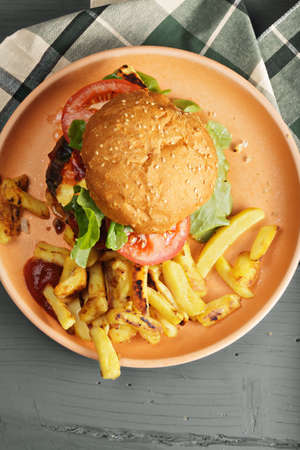 tabletop: Burger and potato fries on a wooden tabletop above view