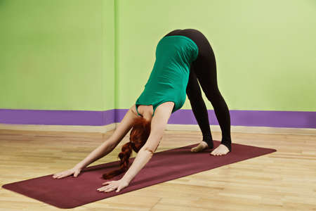 tibetian: Woman exercising bending back while leaning on hands pose which is fifth in Tibetian yoga set