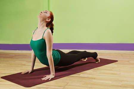 curving: Woman exercising curving back final pose at Tibetian yoga set Stock Photo