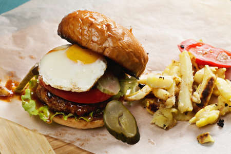 sunny side: Sunny side up burger served with fried potatoes Stock Photo