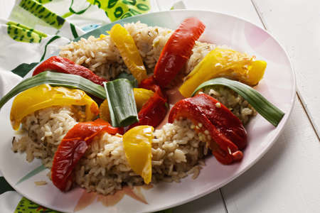 ovenbaked: Risotto with oven-baked bell peppers on a white wooden tabletop closeup