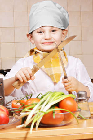 pleasant emotions: Positive little cook with two knives at the kitchen