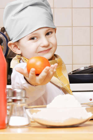 pleasant emotions: Cute little cook giving tomato while standing at the kitchen table