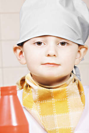 tiled wall: Portrait of little cook against tiled wall