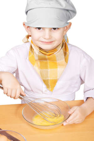 pleasant emotions: Little smiling cook whisking eggs in a bowl against white background
