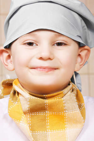 tiled wall: Portrait of smiling little cook against tiled wall