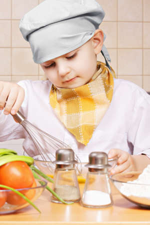 whisking: Little cook whisking eggs in a bowl at the kitchen Stock Photo