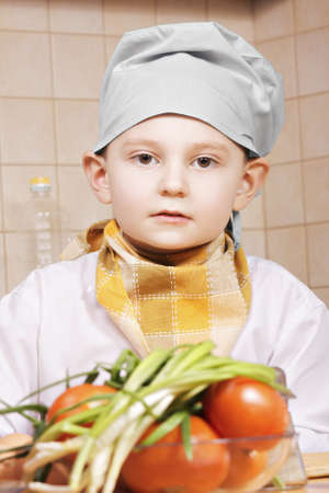 tiled wall: Portrait of little cook with tomatoes against tiled wall
