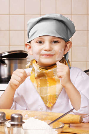 pleasant emotions: Smiling little cook standing at the kitchen face stained with flour