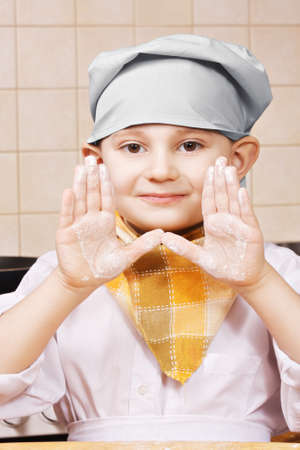 pleasant emotions: Little cook showing hands stained with flour at the kitchen