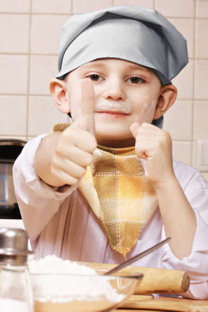 pleasant emotions: Contented little cook face stained with flour showing thumb up at kitchen Stock Photo