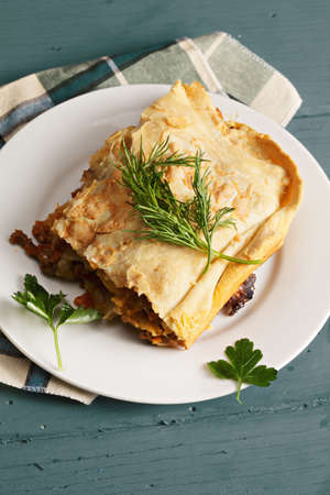 tabletop: Plate with lasagna on a wooden tabletop
