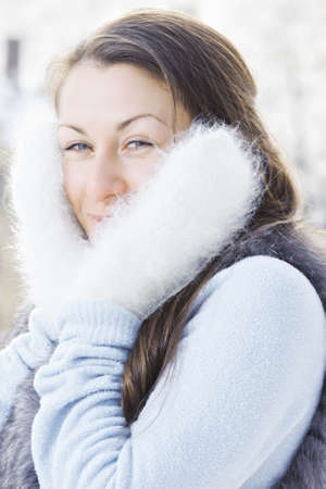 pleasant emotions: Young caucasian woman in fluffy mittens standing outdoors