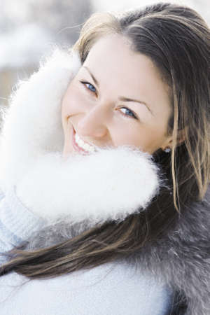 pleasant emotions: Young caucasian happy woman in fluffy mittens standing outdoors Stock Photo