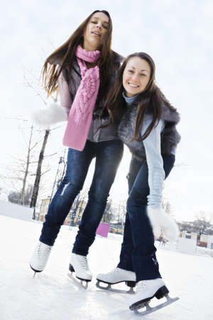 pleasant emotions: Two young women on ice rink low angle view