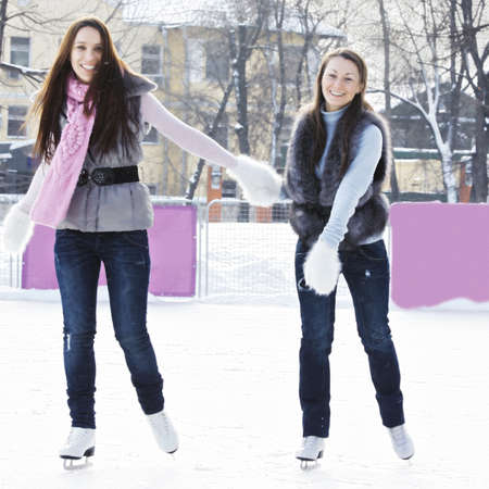 ice rink: Smiling women skating on ice rink holding each other hands