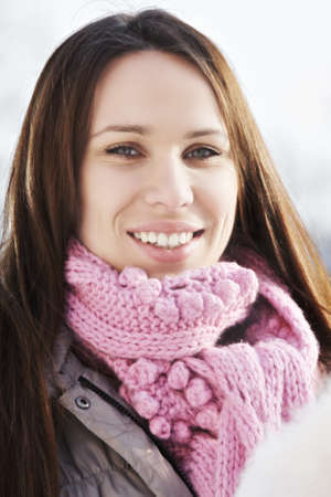 pleasant emotions: Smiling young caucasian woman wearing pink scarf outdoors in a winter day Stock Photo