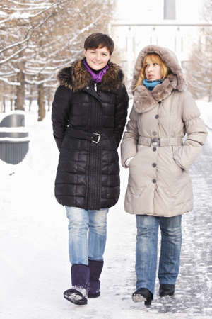 going in: Two young women going in a winter day and talking