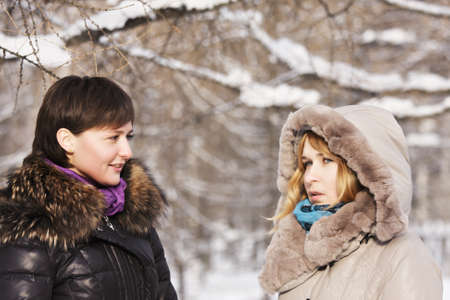 Two young women talking outdoors at winter day