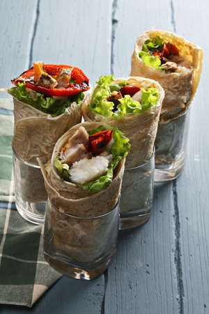 burrito: Burittos with rice and roasted chicken on a wooden tabletop