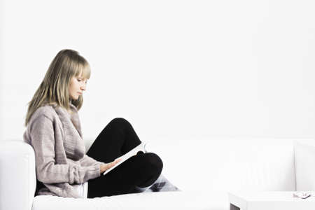 sideview: Young blonde caucasian woman reading book on a white sofa sideview Stock Photo