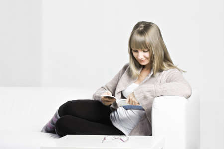 pleasant emotions: Young positive caucasian woman reading book while sitting on a leather white sofa against gray wall