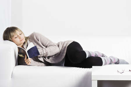 laying down: Young blonde caucasian woman reading with comfort while laying down on a white couch