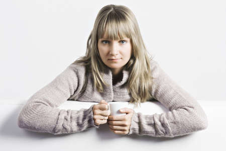 Serious young blonde caucasian woman with white cup photo