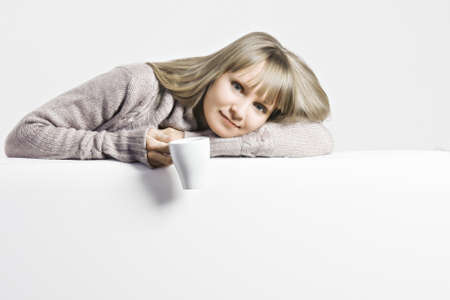 Young blonde caucasian woman with white cup leaning on a sofa back photo