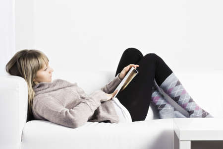 woman laying down: Young caucasian woman laying down on a white couch and reading Stock Photo