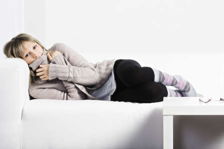 Young blonde caucasian woman laying down on a white couch photo