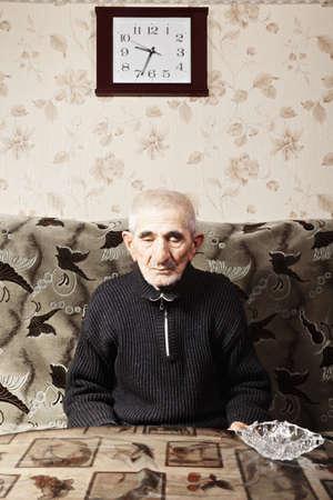 grayness: Pensieroso uomo anziano caucasica in abbigliamento casual, seduto sul divano a tavola Archivio Fotografico
