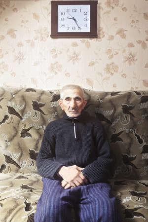 hombre viejo: Hombre cauc�sico mayor en ropa casual sentado en el sof� bajo el reloj de pared