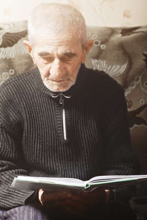 grayness: Senior caucasian man reading book while sitting on couch Stock Photo