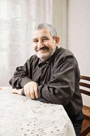 grayness: Contented anziano caucasica uomo seduto a braccia piegate tavolo Archivio Fotografico
