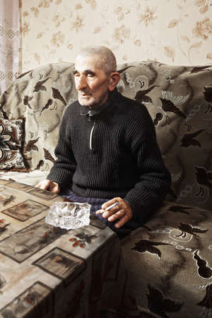 grayness: Anziano caucasica uomo seduto sul divano a tavola con la sigaretta