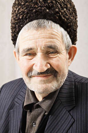 grayness: Senior caucasian man in shipskin hat closeup portrait