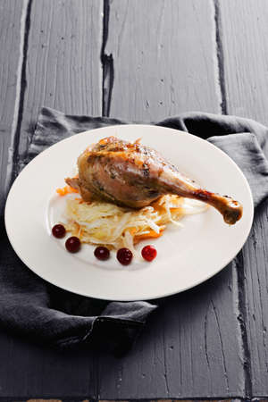 tabletop: Duck leg confit served with sauerkraut on a wooden tabletop Stock Photo