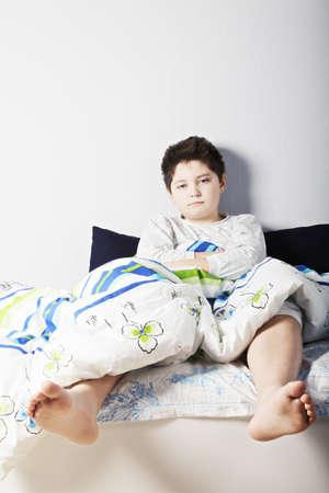 awakened: Awakened caucasian brunette boy sitting on the bed leaning on wall