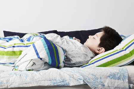 cosiness: Morning sleep of caucasian boy laying down in bed closeup