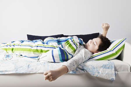 wakening: Wake up of contented caucasian boy laying down in bed at sunny bedroom Stock Photo