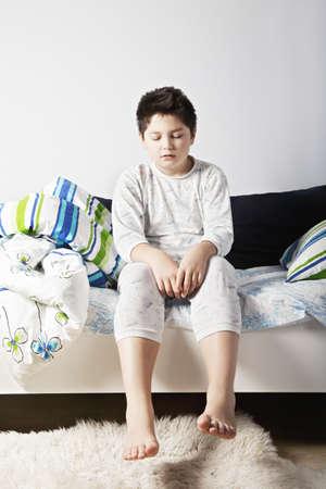 wakening: Sleepy caucasian brunette boy sitting on the bed eyes closed
