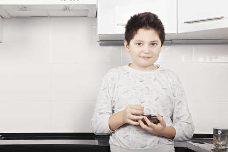 pleasant emotions: Brunette caucasian boy standing with cereal bowl at the kitchen closeup