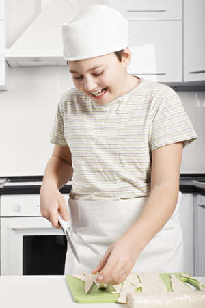pleasant emotions: Happy caucasian boy slicing dough while cooking at the kitchen Stock Photo