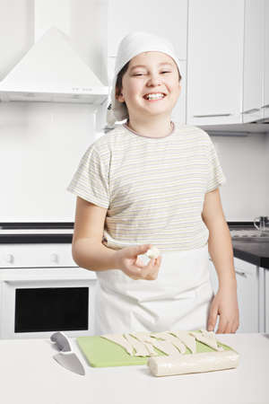 pleasant emotions: Smiling caucasian boy holding raw croissant made by himself while standing at the kitchen Stock Photo